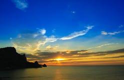 与被覆盖的橙色天空和山剪影的美好的日落 库存图片