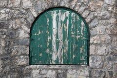 与被钉牢的绿色木快门的古老半圆窗口 图库摄影