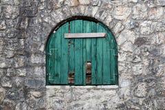 与被钉牢的绿色木快门的古老半圆窗口 库存图片