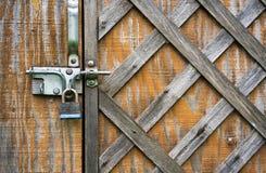 与被锤击的板条的木门是闭合的在挂锁 库存照片