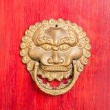 与被镀金的螺柱和狮子顶头通道门环的古老红色门 免版税库存照片