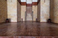 与被隐藏的框架石头砖墙和木地板围拢的两根大理石柱的适当位置 库存照片