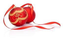 与被隔绝的丝带弓的两个红色圣诞节装饰球 免版税库存照片