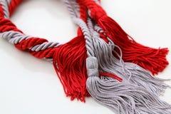 与被隔绝的缨子的灰色和红色绳索 库存图片