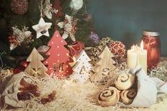 与被雕刻的信件xmas和圣诞节甜点的四棵装饰木圣诞树 T 免版税库存照片