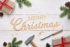 与被雕刻的文本的平的圣诞节问候到与凿子和锤子的白色木表面里 库存照片