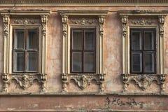 与被雕刻的框架的三个窗口在老房子的门面 免版税库存照片