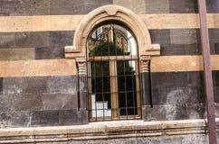 与被雕刻的专栏和装饰钢格栅的被成拱形的窗口开头 免版税库存图片