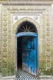 与被雕刻的石装饰的古老蓝色门 免版税库存图片
