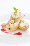 与被鞭打的奶油、坚果、薄菏、蜂蜜和果酱的自创水煮的梨 免版税库存图片