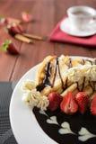 与被鞭打的奶油、巧克力和草莓的薄煎饼 免版税库存照片