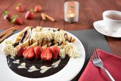 与被鞭打的奶油、巧克力和草莓的薄煎饼 免版税图库摄影