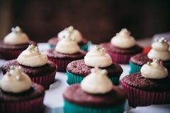 与被鞭打的奶油和方旦糖珍珠冠上的红色天鹅绒杯形蛋糕 免版税库存照片