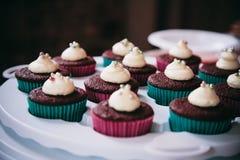 与被鞭打的奶油和方旦糖珍珠冠上的红色天鹅绒杯形蛋糕 图库摄影