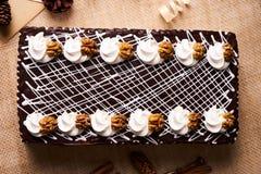 与被鞭打的奶油和核桃的巧克力蛋糕 免版税库存照片