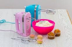 与被鞭打的奶油和蛋糕的桃红色和蓝色厨房搅拌器在t 库存照片