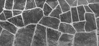 与被风化的板岩的老石墙背景在黑白 库存照片