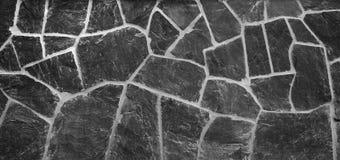 与被风化的板岩的老石墙背景在黑白 免版税图库摄影