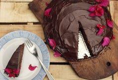 与裁减片断的巧克力蛋糕在木背景 库存图片