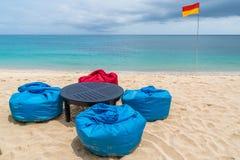 与装豆子小布袋和桌的热带海滩在沙子 图库摄影