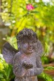 与装饰加尔德角的翼的逗人喜爱的石天使丘比特雕塑 免版税库存图片