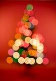 与装饰和光bokeh的多颜色圣诞树 库存照片