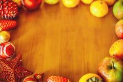 与装饰和果子的圣诞节背景在与拷贝空间的木桌上 免版税库存图片