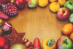 与装饰和果子的圣诞节背景在与拷贝空间的木桌上 免版税库存照片
