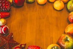 与装饰和果子的圣诞节背景在木桌上 被定调子的图象 免版税库存照片