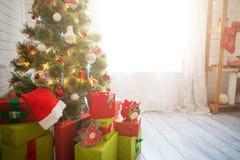 与装饰和礼物的典雅的圣诞树在窗口的典雅的硬木地板上 免版税库存图片
