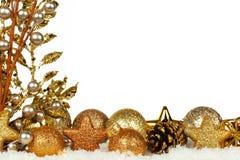 与装饰品和分支的金黄圣诞节边界在新鲜的雪 免版税库存图片