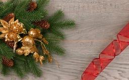 与装饰品的新年云杉的分支在与一条红色丝带的黑暗的背景 免版税库存图片