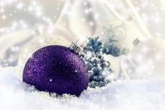 与装饰品的豪华紫色圣诞节球在圣诞节斯诺伊风景 免版税库存图片