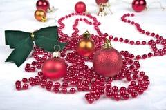 与装饰响铃的圣诞节背景,在白色的丝带 库存照片