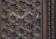 与装饰安心的古老棕色木门 免版税库存图片