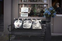 与装饰枕头的铸铁长凳在商店附近 图库摄影