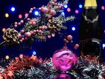 与装饰球的圣诞树分支 诗歌选,瓶香槟 免版税库存照片