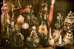 与装饰的不可思议的瓶和灼烧的蜡烛的巫婆桌 库存图片