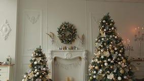 与装饰的冷杉木、壁炉、灯笼、灯、蜡烛、花圈、爆沸和礼物的时髦的白色圣诞节内部 影视素材