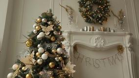 与装饰的冷杉木、壁炉、灯笼、灯、蜡烛、花圈、爆沸和礼物的时髦的白色圣诞节内部 股票视频