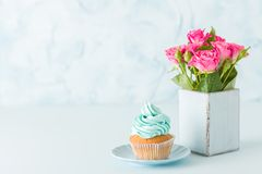 与装饰的蓝色淡色水平的横幅用奶油色杯形蛋糕和桃红色玫瑰在减速火箭的破旧的别致的花瓶 免版税库存图片