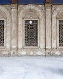 与装饰的铁栅格的三个毗邻被成拱形的窗口在白色大理石 库存图片