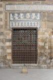 与装饰的铁栅格的木窗口在石砖墙 库存图片
