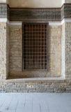 与装饰的铁栅格的被隐藏的木窗口在石砖墙 免版税库存照片