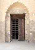 与装饰的铁栅格的被隐藏的木窗口在石砖墙 库存图片