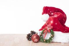 与装饰红色圣诞老人帽子和雪花的圣诞节桌 图库摄影