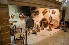 与装饰铜厨具的大石壁炉和椅子在卢尔马兰防御 免版税库存照片