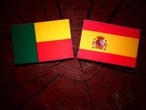 与西班牙旗子的贝宁旗子在树桩 库存照片