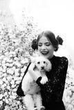 与西班牙构成的愉快的女孩举行狗,在头发上升了 免版税库存图片