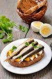 与西鲱和鸡蛋的开胃菜面包在白色板材 免版税图库摄影